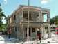 researcher surveys a damaged residence in Haiti