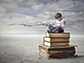 a kid sitting on a stack of books reading