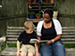 a lady and child sitting on a bench reading a book