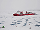 science team working on an ice station in front of the icebreaker XueLong