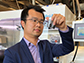 Zheng Chen holds vials of recycled cathode particles
