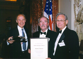Image of the Science Service accepting the Award from Michael Ambrosino, Committee Chair.  (L-R) Dudley Herschbach, Chairman of the Board and Donald Harless, President