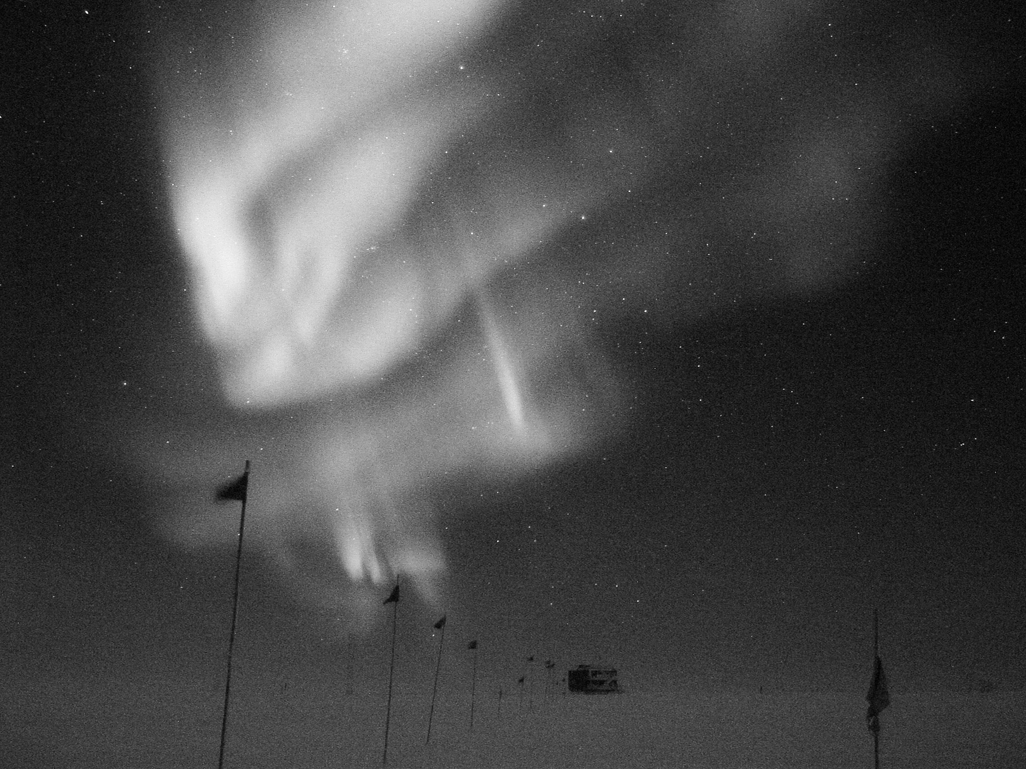 Southern Lights, over the flagline to a building at NSF's Amundsen-Scott South Pole Station; caption is below