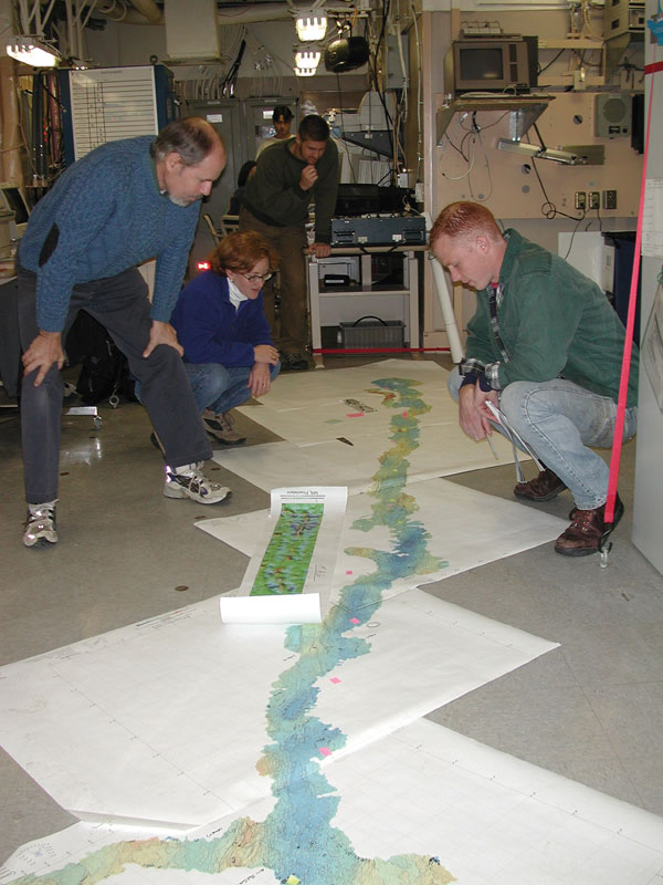 Researchers pore over a map of the Gakkel Ridge aboard Coast Guard Cutter Healy in 2001. NSF Photo